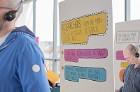 Two people listening to stories and an information board about cancer research